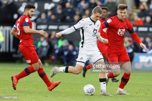 George Byers of Swansea City takes a shot against Sam Morsy and Lee Evans of Wigan Athletic during the Sky Bet Championship match between Swansea...