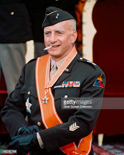 George C Scott , US actor, in ceremonial military uniform, with an orange sash, and smoking a cigarette in a publicity still issued for the film,...