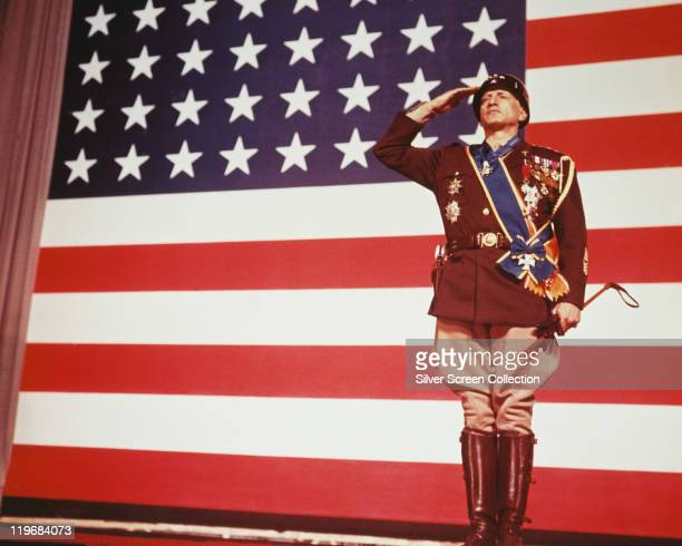 George C Scott , US actor, saluting in uniform as he stands before a large stars-and-stripes flag in a publicity still issued for the film, 'Patton',...