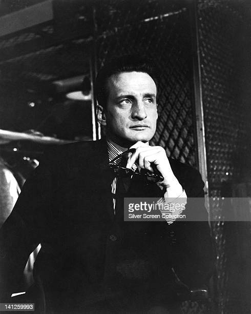 George C Scott , US actor, wearing a black suit over a striped shirt, holding a pair of sunglasses below his chin, in a publicity still issued for...