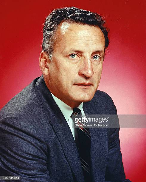 George C Scott , US actor, wearing a dark grey jacket over a white shirt and a red, black and white striped tie in a studio portrait, against a red...