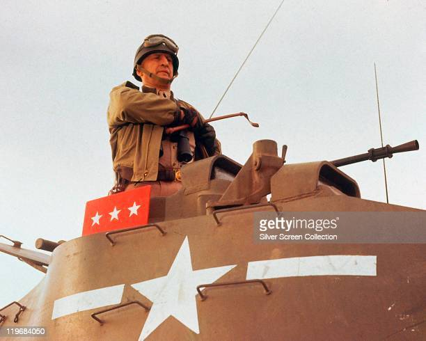 George C Scott , US actor, wearing a helmet with goggles, standing in the gun turret of a tank, and holding a riding crop in a publicity still issued...
