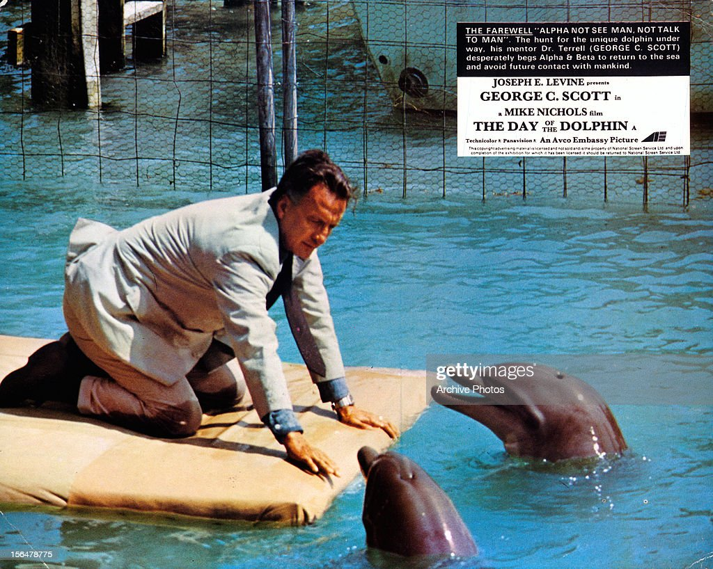 George C Scott with two dolphins in a scene from the film