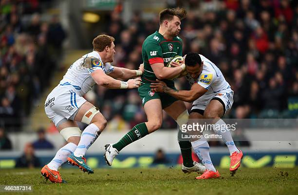 George Catchpole of Leicester tigers is tackled by Sam Simmonds and Fetu'u Vainikolo of Exeter Chiefs during the LV= Cup Semi Final between Leicester...