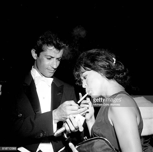 George Chakiris lights Rita Moreno cigarette at an event in Los Angeles,CA.