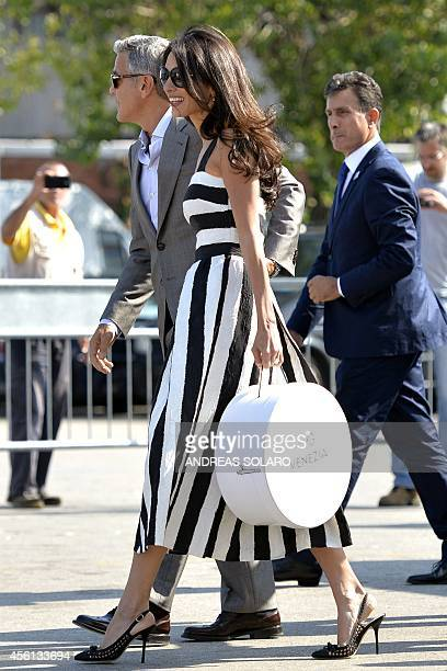 George Clooney and his Lebanonborn British fiancee Amal Alamuddin holding a bag bearing the logo AG arrive at Venice's Piazzale Roma in Venice on...