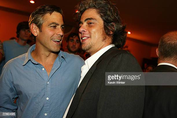 George Clooney chats with Benicio Del Toro at the premiere of Full Frontal at the Landmark Cecchi Gori Fine Arts Theater in Los Angeles CA on Tuesday...