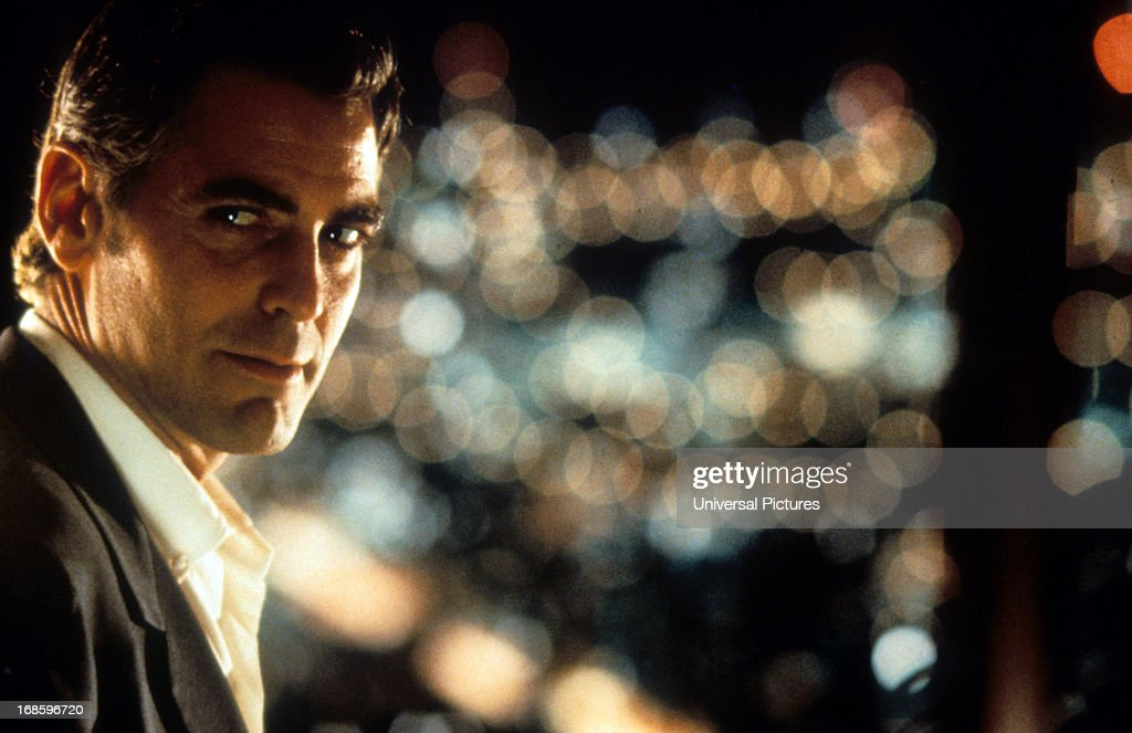 George Clooney looking to his right with the city lights as a backdrop in a scene from the film 'Out Of Sight', 1998.