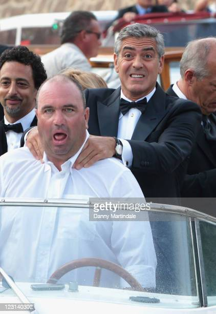 George Clooney plays with the driver of his river taxi at the 68th Venice Film Festival on August 31, 2011 in Venice, Italy.