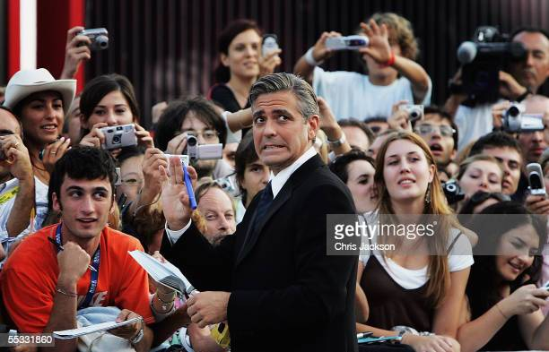 George Clooney signs autographs for fans as he arrives for the Golden Lion Awards at the Palazzo del Cinema on the final day of the 62nd Venice Film...