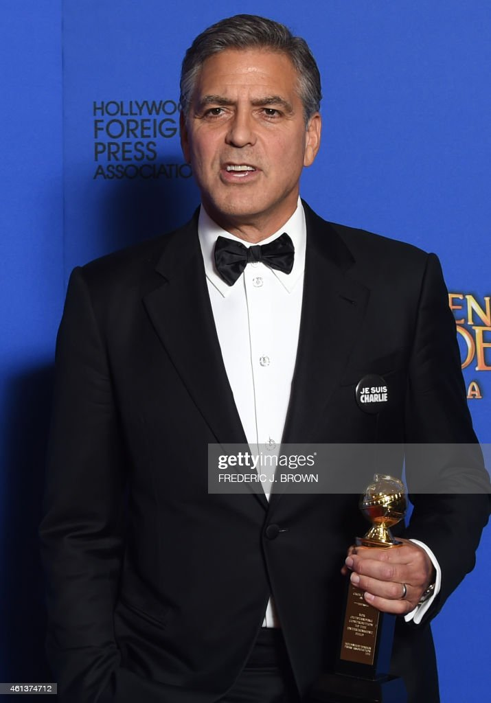George Clooney, wearing a 'Je suis Charlie' button, poses with the Cecil B. DeMille Award, in the press room at the 72nd annual Golden Globe Awards, January 11, 2015 at the Beverly Hilton Hotel in Beverly Hills, California. AFP PHOTO / FREDERIC J BROWN / AFP PHOTO / Frederic J. BROWN