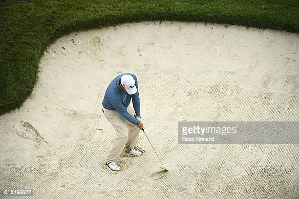 George Coetzee of South Africa hits from a bunker on the 18th hole during day one of the WGC - HSBC Champions at Sheshan International Golf Club on...