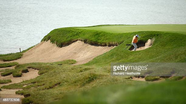 George Coetzee of South Africa hits out of the bunkers during a practice round prior to the 2015 PGA Championship at Whistling Straits on August 12,...