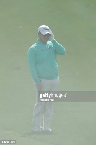 George Coetzee of South Africa waits for a sand storm to pass on the 12th hole during the second round of the Omega Dubai Desert Classic at Emirates...