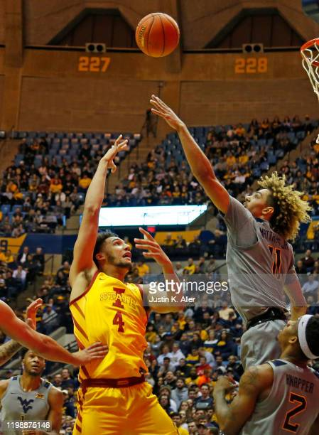 George Conditt IV of the Iowa State Cyclones takes a shot against Emmitt Matthews Jr #11 of the West Virginia Mountaineers at the WVU Coliseum on...
