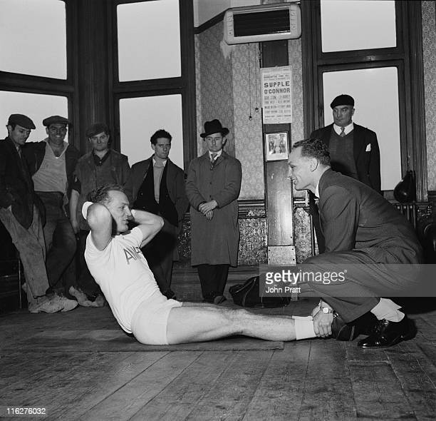 George Cooper assists his twin brother Henry during a training session at the Thomas a Becket gym on the Old Kent Road South London 19th November...