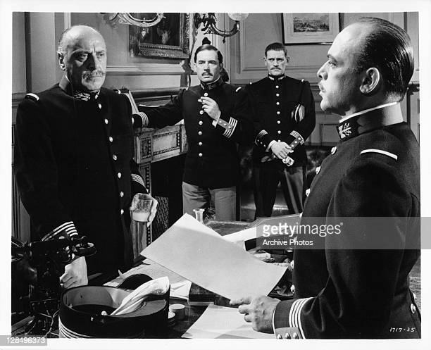 George Coulouris listens to Herbert Lom as Leo Genn and Harry Anders watch in a scene from the film 'I Accuse' 1958