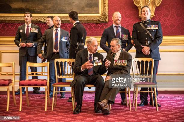 George Cross recipient Alf Lowe talks with Victoria Cross recipient Keith Payne while other GC and VC recipients wait before having an official...