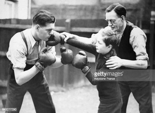 George Danahar à gauche entraîne son petit frère Arthur à la boxe sous la direction de leur père dans leur jardin de Bethnal Green le 7 mars 1939 à...