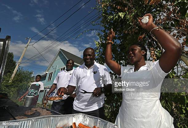 George Darteh left and Victoria Smith right assist Harry Danso a royal chief from the Ashanti tribe in Ghana as he manned the grill at a cookout for...