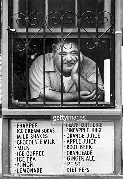 George DeMarco watches pedestrians from the window of DeMarco Roast Beef on Hanover Street in Boston's North End on Sept 22 1978 A sign below lists...