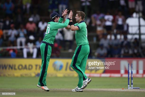 George Dockrell and Boyd Rankin of Ireland celebrate the wicket of Kyle Coetzer of Scotland during The Cricket World Cup Qualifier between Ireland...