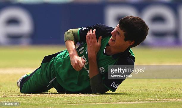 George Dockrell of Ireland injures his right shoulder trying to stop a ball to the boundary during the 2011 ICC World Cup match between Ireland and...