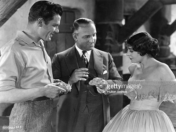 George Duryea director Allan Dwan and Renee Adoree look at some gold ore on the set of the MGM film 'Tide Of Empire' set at the time of the...