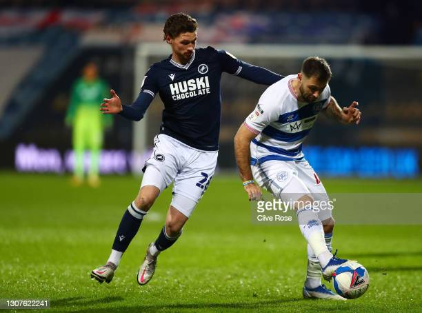 George Evans of Millwall FC and Charlie Austin of Queens Park Rangers battle for the ball during the Sky Bet Championship match between Queens Park...