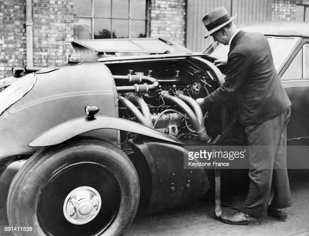 George Eyston vérifiant le moteur de sa voiture aérodynamique avant de tenter un nouveau record du monde de vitesse sur terre aux EtatsUnis le 10...