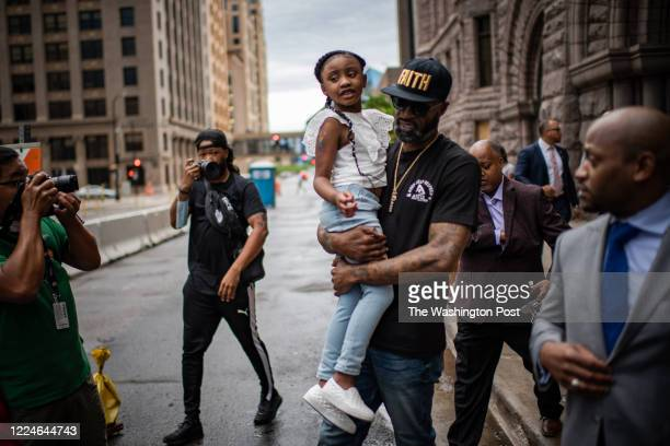 George Floyd's daughter Gianna is carried by former NBA players and family friend Stephen Jackson after a press conference at the Minneapolis City...