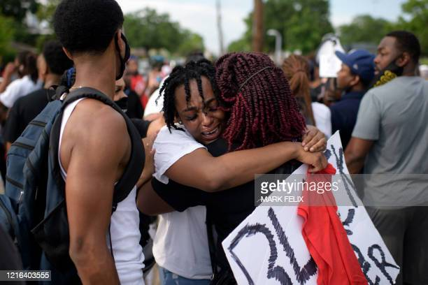 TOPSHOT George Floyd's niece Gabrielle Thompson cries as she hugs another woman during a Justice for George Floyd event in Houston Texas on May 30...