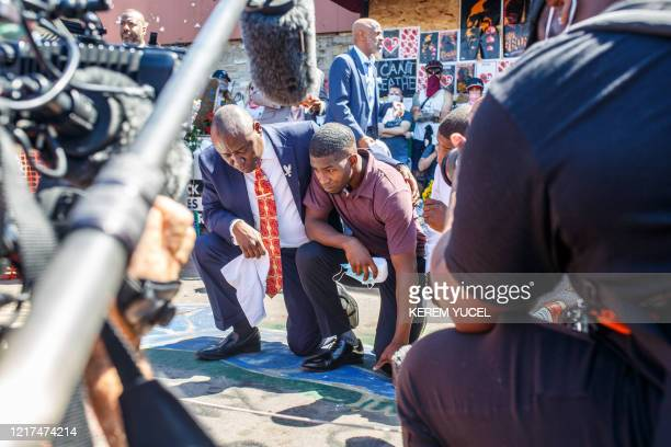 TOPSHOT George Floyd's son Quincy Mason Floyd and family Attorney Ben Crump pray on June 3 at the site where George Floyd died in Minneapolis...