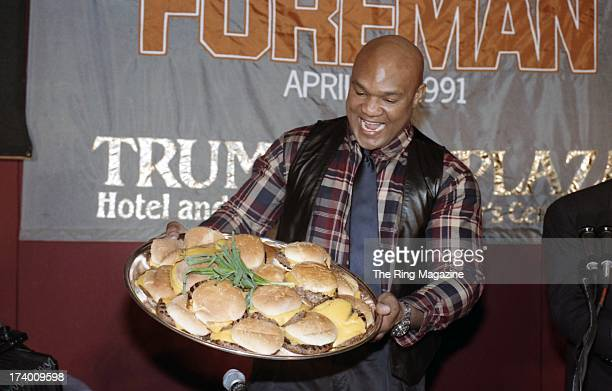 George Foreman poses with a platter of Hamburgers during a press conference to promote his upcoming fight on April 191991 in Atlantic City New Jersey