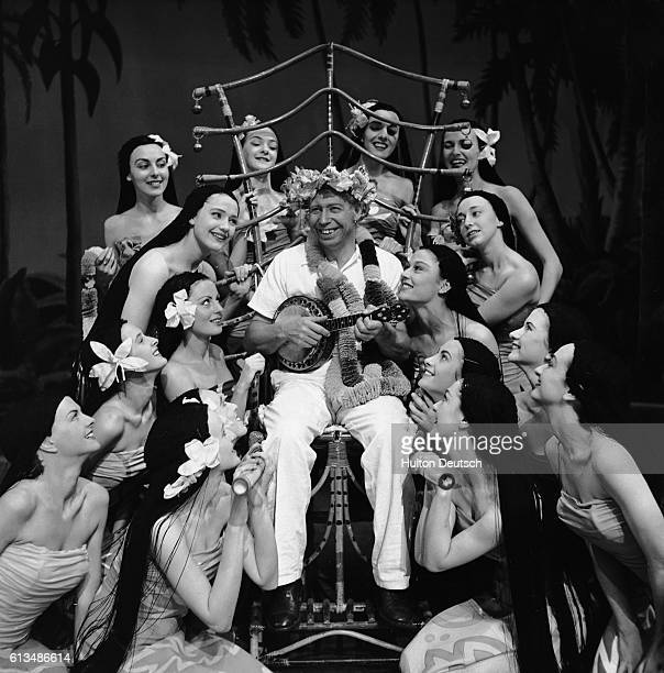 George Formby entertains some hoola girls in the show Zip goes a million 1951