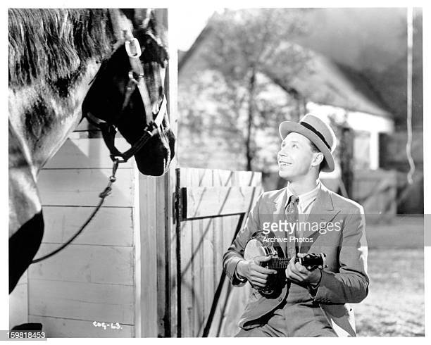 George Formby plays a banjo to a horse in a scene from the film 'Come On George' 1939