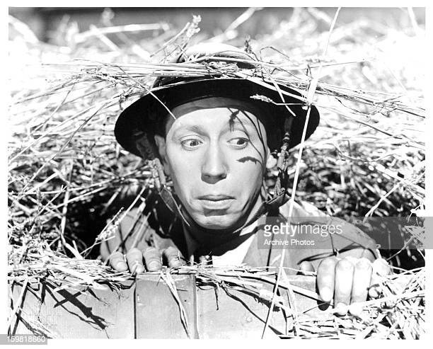 George Formby poking his head out from below floorboard in a scene from the film 'Spare A Copper' 1940 Photo by Associated British Film Distributors...