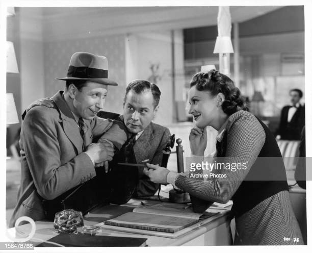George Formby smiling at Phyllis Calvert with Hal Gordon in between them in a scene from the film 'To Hell With Hitler' 1940