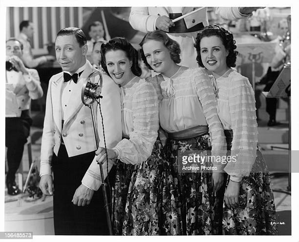 George Formby standing in front of microphone with song girls behind him in a scene from the film 'To Hell With Hitler' 1940