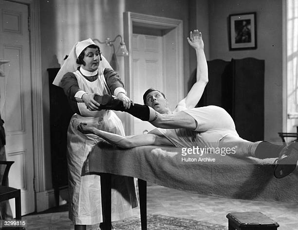 George Formby the British comedian and ukelele player is wrestling with a nurse who is trying to remove his clothes in a scene from 'Keep Your Seats...
