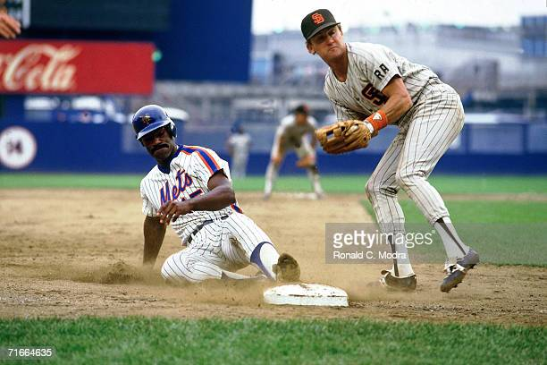 George Foster of the New York Mets slides into third base as Graig Nettles of the San Diego Padres looks at the umpire at Shea Stadium during an...