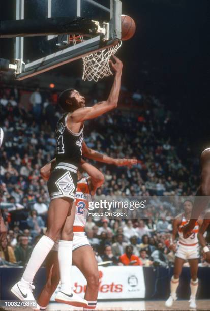 George Gervin of the San Antonio Spurs goes in for a reverse layup against the Washington Bullets during an NBA basketball game circa 1980 at the...