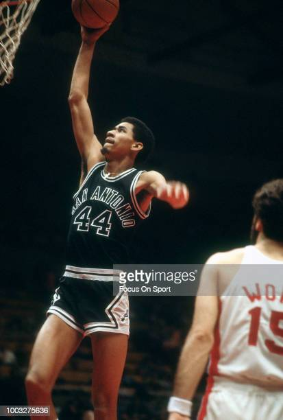 George Gervin of the San Antonio Spurs goes up for a slam dunk against the New Jersey Nets during an NBA basketball game circa 1980 at the Rutgers...