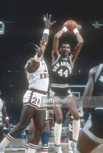 George Gervin of the San Antonio Spurs looks to pass over the top of Campy Russell of the New York Knicks during an NBA basketball game circa 1981 at...