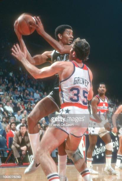 George Gervin of the San Antonio Spurs looks to pass the ball over Kevin Grevey y#35 of the Washington Bullets during an NBA basketball game circa...