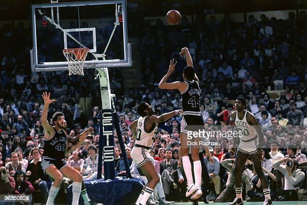 George Gervin of the San Antonio Spurs shoots a jump shot against ML Carr and Robert Parish of the Boston Celtics during a game played in 1982 at the...