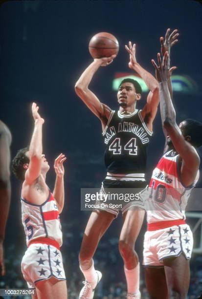 George Gervin of the San Antonio Spurs shoots Kevin Grevey and Bob Dandridge of the Washington Bullets during an NBA basketball game circa 1978 at...