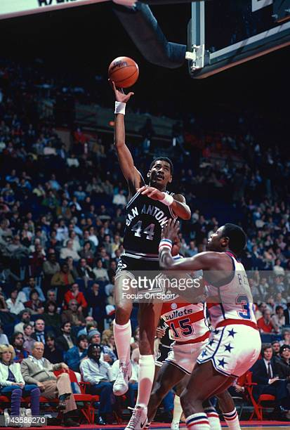 George Gervin of the San Antonio Spurs shoots over Billy Ray Bates of the Washington Bullets during an NBA basketball game circa 1982 at the Capital...