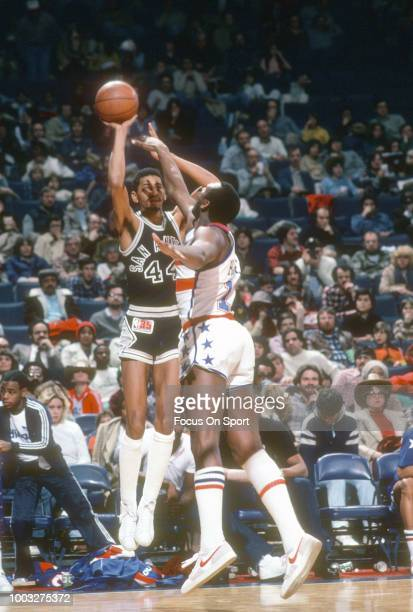 George Gervin of the San Antonio Spurs shoots over Elvin Hayes of the Washington Bullets during an NBA basketball game circa 1980 at the Capital...