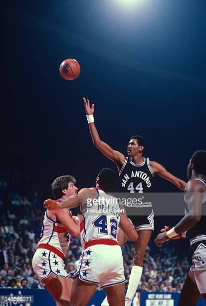 George Gervin of the San Antonio Spurs shoots over Jeff Ruland and Greg Ballard of the Washington Bullets during an NBA basketball game circa 1982 at...